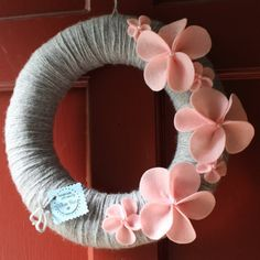 Grey Yarn Wreath with Pink Plumeria flowers. I'm in love with this wreath.