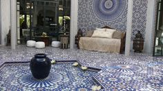 Outdoor lounge area with fountain and Moroccan mosaics