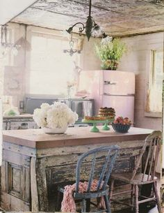 Love the old tin ceiling and shabby island in this vintage kitchen.