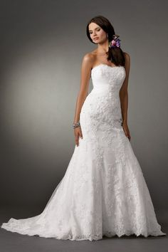 Strapless lace fit and flare wedding gown with tulle draped bodice. Buttons and loops on center back. Semi cathedral train. Removable spaghetti straps included.