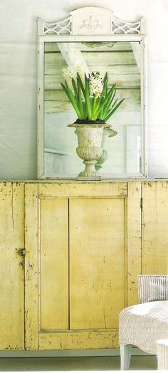 Vintage painted cabinet, ticking stripe slipcover, bulbs in a cast iron urn. Soft palette
