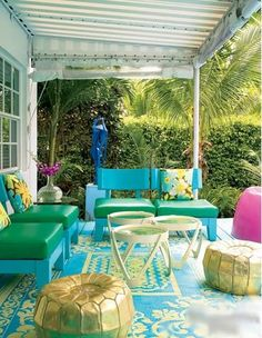 eclectic patio - covered patio deck, gold metallic pouf, yellow and blue outdoor rug, green and blue outdoor furniture