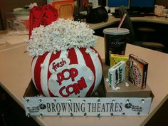 """Made for work pumpkin contest.  Painted pumpkin to look like old fashioned popcorn box. Strung popcorn on thread with needle. Glued round florist foam to top for heigth, then glued popcorn strands in """"realistic mess"""".  Attached 2 larger than normal  """"admit one"""" tickets with glue to foam.  Used empty soda cup & empty candy boxes. Cut out holes in small box to keep candy/cup in place.  Placed all in a box lid. Used battery operated lights & polked wholes thru box to mimic """"marquee look""""."""