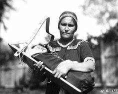 Ojibway woman wearing jingle dress holding baby in cradle board