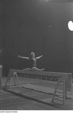 Gymnast performing splits on balance beam (1950).