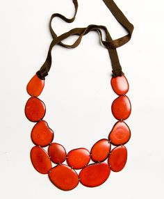 This stunning  (and eco-friendly!) bib necklace is the perfect complement to a formal dress, but needs nothing more than a white tee shirt to shine! Available in vivid Teal and warm Coral.