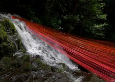 Red strings suspended over waterfall pool to form installation.