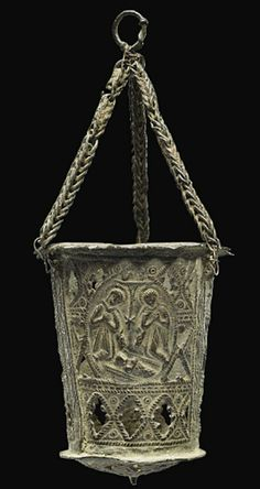 A PIERCED METAL INCENSE BURNER   ENGLISH, 14TH OR 15TH CENTURY  The tapering cylindrical body with three suspension cords attached to the upper rim and with relief decoration including three scenes of the Nativity; minor losses and damages  3¼ in. (8.3 cm.) high, the body