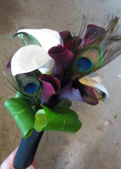 Mix of Full size white calla lilies and black mini calla lilies. Peacock feathers and rolled lemon leaf finish of the bouquet