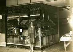 Woman standing outside a fruit shop in Puckle Street, Moonee  Ponds, date unknown.