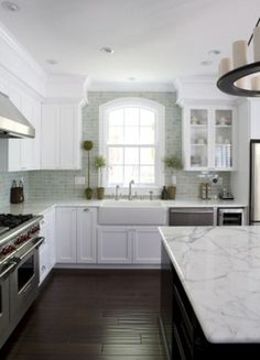 white...marble...(subway)tile to the ceiling....dark floors...big slab of an island...