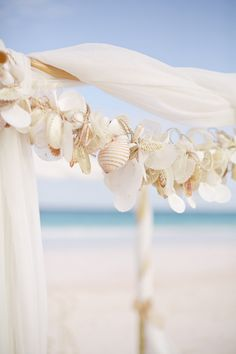 Arch detail for a beach #wedding altar - pretty shell garland!