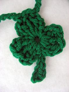 Shamrock:  Chain 4, join with a slip stitch in first chain to form a ring.  Petal (make 3): Chain 3, trc, dc, trc, ch 3, slip stitch in ring.  Stem: Chain 4, slip stitch in 2nd chain from hook, and remaining two chains. Fasten off.  Weave in ends.