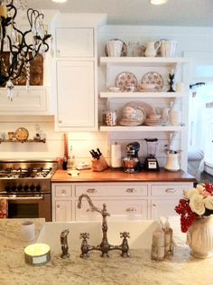 open shelves flanked by cupboards  counters: granite/kashmir white/ honed + walnut