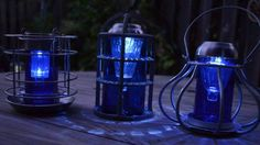 """Sensational Recycled Solar Lights in the Garden  """"These were a couple of wire candle holders found at a thrift store. Cut the tops off a couple of cobalt Blue Bud bottles then set a solar light on the top. The center one is an aluminum cover used to protect lights usually found in commercial buildings. They cast a cool design on the table at night. See these two and three more brilliant and easy projects"""