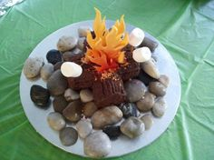 1/4 sheet,halved and layered, carved in to shape of logs,covered in chocolate buttercream ; cinnamon and orange cream sprinkles to look like glowing embers in a fire pit. Marshmallows and  rock shaped cake balls complete the look.