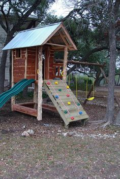 tree house with rock climbing wall, slide and deck