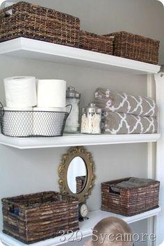 bathroom shelves with baskets instead of medicine cabinet.