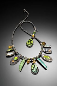 Jeanie Pratt  Sterling silver, fine silver, 22K gold, 18K gold, 14K gold, birdwing butterfly (Ornithoptera priamus) wings, beetle wings (Chrysina spectabilis, Chrysina gloriosa, & Chrysochroa purpureiventris), opal, ammolite, star sapphire, amber (with insect inclusions), rutilated quartz, citrine, green topaz, peridot, freshwater pearls, enamel, resin    Bobbin lace, knitting, looping, stitching, etching, enamel, fabrication