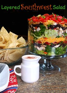 This beautiful Layered Southwest Salad is as simple and delicious as it is gorgeous.  It's perfect for company or just lunch at home with the kids.  The crispy, fresh greens, crisp summer veggies and grilled chicken make it one of my favorite go-to summertime lunches.  I bet it will be one of yours, too.  Click over to Busy-at-Home and get the recipe!  #salad #lunch #summer #recipe #easyrecipe