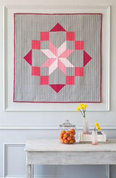 This understated quilted wallhanging features pink gradations of a large center star and frame on a gray background. Digital pattern available! #QuiltPattern #Wallhanging #ModernQuilt