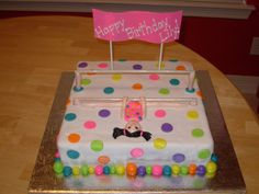 Gymnastics Party Cake - This cake was based on a photo of the birthday girl that was included on her invitation.  The phtoo showed the girl doing the splits on the low bar hanging upside down.  The colors were all the colors in her leotard for the party.  The bars are wooden dowels, the girl is made of gumpaste.