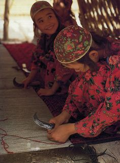 Turkmen girls weaving a traditional tribal carpet on a horizontal loom. After making the knot they cut the tufts of the pile with a curved knife.  Thompson, Jon. Carpet Magic: The art of carpets from the tents, cottages and workshops of Asia. UK: Barbican Art Gallery, 1983, 57.