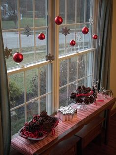 Hang ornaments from horizontal branch above back table or info table in hallway.