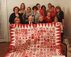 """As a thank you to her aunt, Joanna Rose, for creating a the show of 651 red & white quilts in NYC last year, City Quilter customer & student, Deborah Bingham, had the wonderful idea to make a """"Dear Jane"""" quilt in red & white as a surprise gift. Deborah & her two City Quilter """"Dear Jane"""" teachers, Judy Doenias & Diane Rode Schneck, recruited about 35 past & present Dear Jane classmates to collaborate on this 168 block quilt shown here with Mrs. Rose, husband, Deborah & the other quilters."""