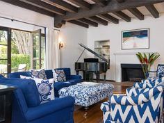 A sitting area comprised of blue and white furniture holds center court in this living room. Designed to accommodate a family of six, the chairs have been retrofitted with swivels for easy TV viewing.