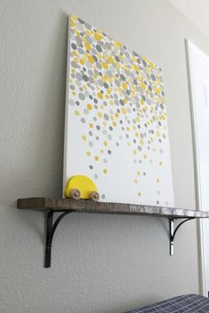 DIY artwork: pick two colors and paint circles of different shades of each. It looks easy, but I'd practice on paper first to get used to it before putting it on a canvas. (More expensive mistake, if you mess up!)