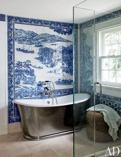 A bath in Shelter Island, New York, sports a mural by Chelsea Arts Tile + Stone; the tub is by Waterworks, with fittings by Lefroy Brooks