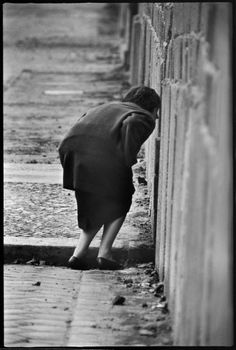 West Berliner looking into East Berlin through a crack in the Berlin Wall at the time of its construction. West Berlin, Germany, November 1961