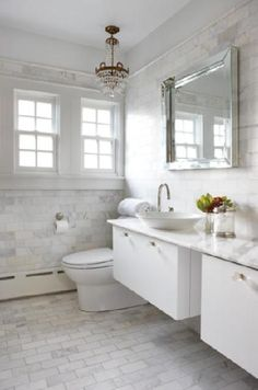 Gorgeous white chic bathroom design with antique brass crystal chandelier, square beveled mirror, overmount round sink, modern floating double vanities with white carrara marble counter tops, glass knobs hardware, white carrara marble subway tiles floors & backsplash and chrome fixtures.