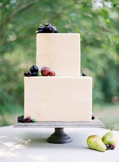 Simple, contemporary and minimalist ivory and fresh fruit tiered wedding cake.