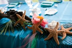 Turquoise and Coral Beach Wedding. (Blue colored table linens were used to offset the turquoise bridesmaids dresses) Wedding Reception head table decor