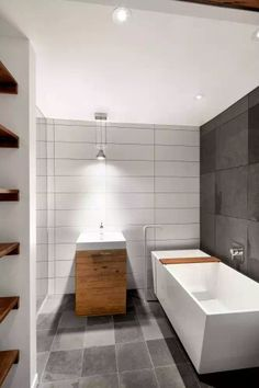 Great stacked oversized subway tiles. White with dark grout. Raw warm wood vanity, shelves to left.