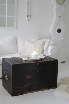 Cottage Chic living room with antique trunk as coffee table. These Trunks were used for luggage in the early 1900's.