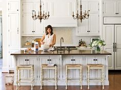 The dark finishes of the floors and the island's top add warmth to the creamy white kitchen. A pair of antique wooden chandeliers over the island completes the look and lends a sense of age to a brand-new house. myhomeideas.com