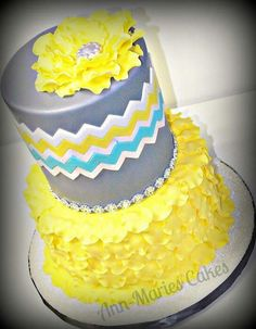 A pretty, modern cake design. Grey, turquoise, and yellow chevron floral cake.