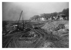 Des Moines Freeway  [I-235] under construction looking west, late 1950's early 1960's. Near the current 6th Avenue exit. Visible in the upper right is one of the surviving neighborhood fire stations. The building still exists today as a private residence. Located SW of DMACC Urban Campus. IN the background is the 9th St. bridge.