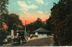 A view of the entrance to Casino Park in Mansfield, Ohio,showing an old car and two boys standing at the entrance.