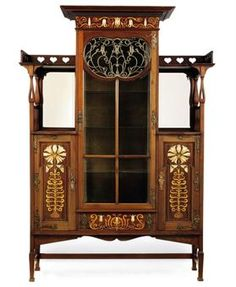 A SHAPLAND & PETTER ART NOUVEAU INLAID MAHOGANY DISPLAY CABINET CIRCA 1900. The central cupboard with glazed door embellished with open metalwork foliage, flanked by pireced, mirrored and galleried shelves above cupboards with elaborate inlaid panels of coloured woods and mother-of-pearl, on tapering supports united by stretchers