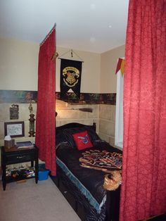 """Harry Potter"" bed - Old jacquard curtains dyed red and hung with Kirsch Universal Track Rod, brooms hung with cafe rod brackets, HP throw & hanging, dragon border purchased off of EBay,"