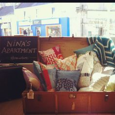 Shop display of cushions in vintage trunk