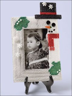 """Snowman Frame  Technique - Plastic Canvas  Display a photo of a loved one in a whimsical, frosty frame for the holiday season or all winter long. This e-pattern was originally published in Plastic Canvas Bazaar Bestsellers.     Size: 7 1/8"""" x 10 1/2"""" (18.1cm x 26.7cm). Made with plastic canvas yarn and 7-count plastic canvas.     Skill Level: Beginner"""