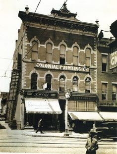 "The Rissler and Stoodt Building stood at 63 1/2 North Main, at the corner of West Dickson and N. Main. This photo shows the building, (which was built in 1880) and its occupants, Dr. Roby DDS, Lucas Drugs and Leech Brothers Furnishings. The Charles Ritter Company occupies the next building to the north. The photo was taken from the east side of N. Main, looking west on W. Dickson. A man walks past Lucas Drugs, later Samilsons. The drugstore awning advertises ""drugs and sodas."""