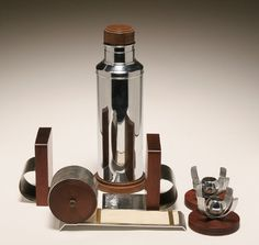 """Modern Art Deco walnut and chrome 6pc assortment; including a Kensington scrolling desk notepad, and Manning Bowman cocktail shaker and candlesticks, and Seymore products bookends. Shaker: 13""""H."""