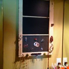 Great for limited space.. Old window with chalkboard paint and knobs to hang jewelry on.