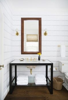 Powder room with iron vanity, leather mirror and gray striped wall paper.
